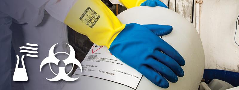 Operaio con guanti resistenti ai prodotti chimici Portwest che manipolano oggetti pericolosi.