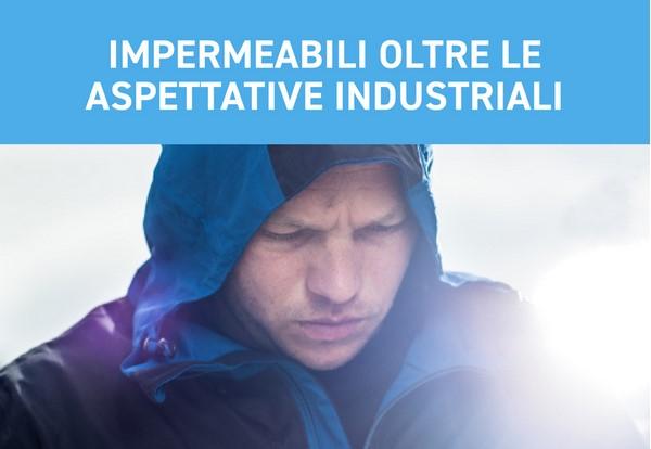 Uomo in giacca antipioggia con cappuccio in testa. Sopra la scritta: Rainwear che supera i requisiti industriali.